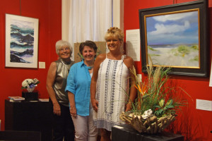Brenda Martin joins Floral Fusion designers Joan McCarthy and Rolanda Cummins in front of FRAMED artists, Bernice Wood and Jack Cochran's work on display in the Red Gallery of the Jailer's House Gallery at the Scott County Arts & Cultural Welcome Center.
